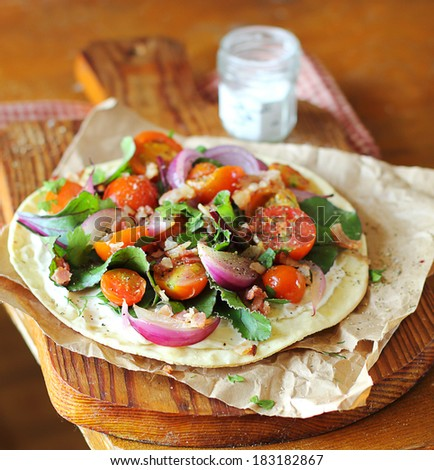 Fresh cherry tomatoes, red onion, green chard leaves and bacon on a wheat flat bread for summer picnic snack - stock photo