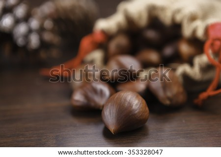 fresh chestnuts in sack bag on wooden table - stock photo