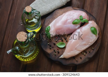 Fresh chicken breast fillets with seasonings and olive oil, high angle view - stock photo