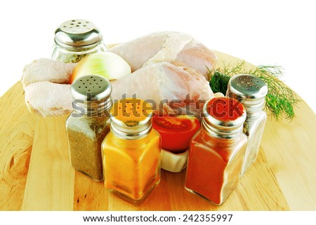 fresh chicken drumstick on wooden plate over white - stock photo