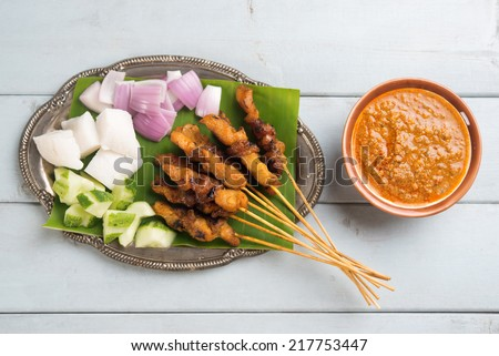Fresh chicken satay on wooden dining table, one of famous Malaysian local dishes. - stock photo