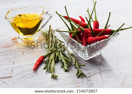 Fresh chili peppers in  bowl  on  table. Fresh rosemary, olive oil. Selective focus. - stock photo