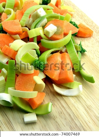 Fresh chopped vegetables on a chopping wooden board - stock photo