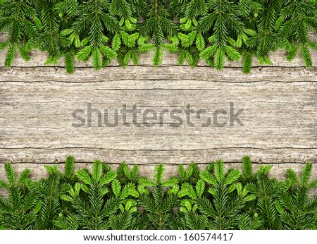fresh christmas tree branches over rustic wooden background. green border from undecorated evergreen twigs - stock photo