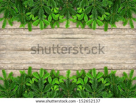 fresh christmas tree branches over wooden background. green border from undecorated evergreen twigs on rustic backdrop - stock photo