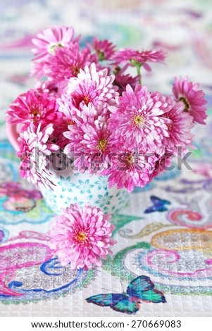 fresh chrysanthemum flowers in a flowerpot on a table  - stock photo