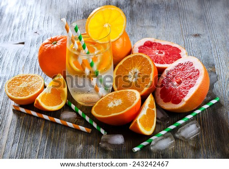 Fresh citrus drink with fruits on wooden background - stock photo