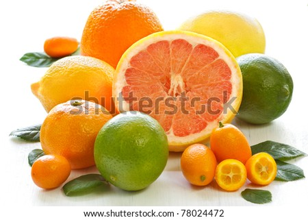 Fresh citrus fruit with leaves on a white garden board. - stock photo