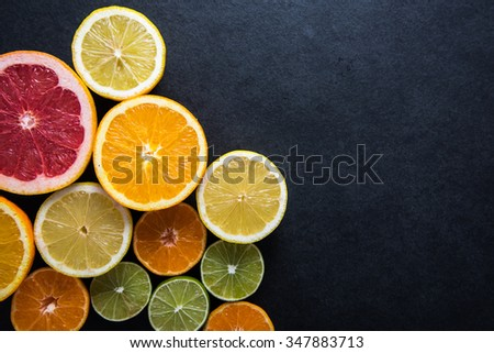 Fresh citrus fruits half cut, dark border background with copy space,from above - stock photo