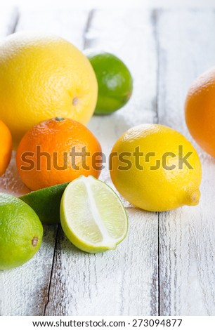 Fresh citrus fruits on white rustic wooden background - stock photo