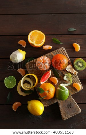 Fresh citrus fruits with green leaves on wooden table, top view - stock photo