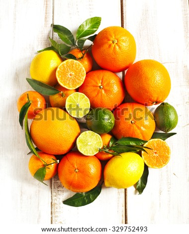 Fresh citrus fruits with leaves on wooden background - stock photo
