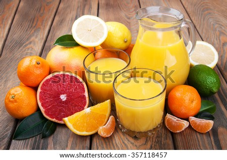 Fresh citrus juice with fruits on a wooden table - stock photo