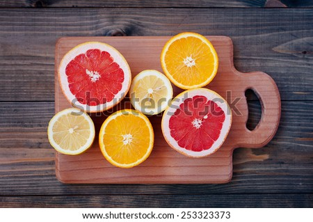 Fresh citrus on color wooden background - stock photo