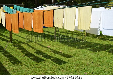 fresh clean hotel towels drying on a line outdoors - stock photo