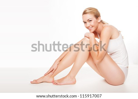 Fresh clean portrait of a long legged beautiful woman in lingerie with a lovely smile sitting on the floor - stock photo