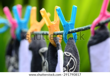 Fresh clean white cotton socks hanging and drying on clothesline  - stock photo