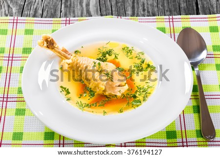 Fresh clear soup with carrot and chicken leg decorated with dill in a wide rim round plate on a napkin with spoon on an old wooden table, top view - stock photo