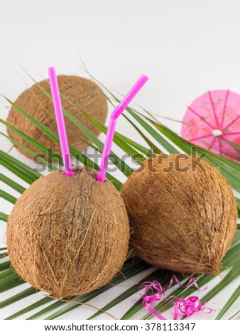 Fresh coconut cocktails with cocktail umbrella placed on coconut leaves - stock photo