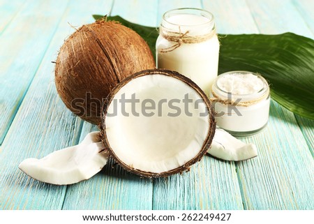 Fresh coconut oil in glassware and green leaf on color wooden table background - stock photo