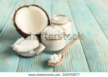 Fresh coconut oil in glassware and wooden spoon on color wooden table background - stock photo