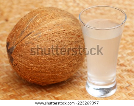 Fresh Coconut with water in a glass on textured surface - stock photo