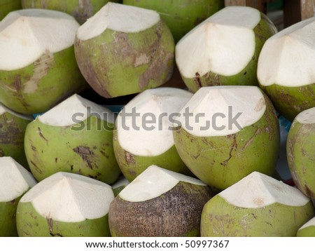 fresh coconuts prepared for sale, closeup and shallow DOF - stock photo