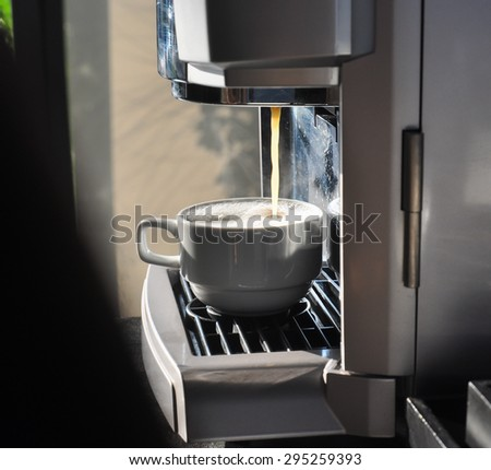 Fresh coffee drops falling to white cup, coffee machine preparing white cup of coffee - stock photo