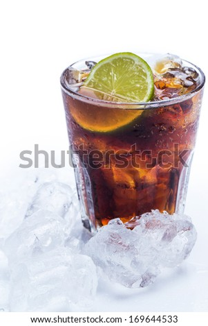 Fresh cola drink with lime fruit and ice - stock photo