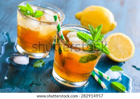 Fresh cold iced tea with mint, ice and lemons, refreshing summer drink with cubes of ice, horizontal on blue background, cocktails, vitamin c - stock photo