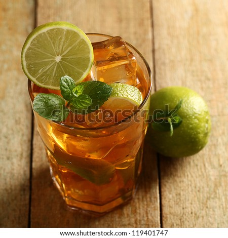 Fresh cold tea with lime, mint and lemon on a wooden surface - stock photo