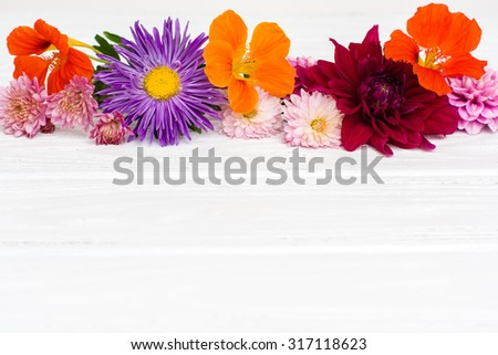 Fresh colorful autumn flowers on white painted wooden planks. Selective focus. Place for text on the bottom of photo. Shallow DOF. - stock photo