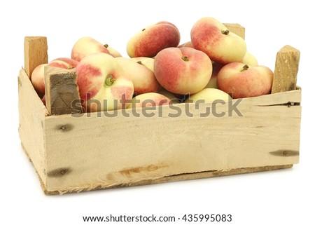 fresh colorful flat peaches (donut peaches) in a wooden crate on a white background - stock photo