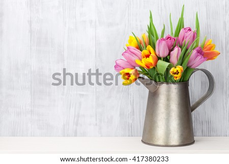 Fresh colorful tulip flowers bouquet on shelf in front of wooden wall - stock photo