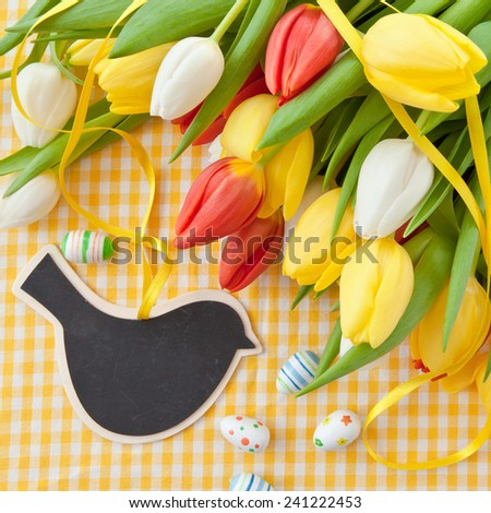 Fresh colorful tulips on yellow plaid fabric - stock photo