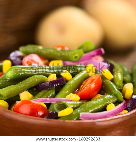 Fresh colorful vegetarian salad made of green beans, cherry tomatoes, sweet corn, black olives and red onions (Selective Focus, Focus one third into the salad)  - stock photo