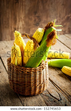 Fresh Corn in a Basket on the wooden table, vertical - stock photo