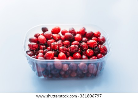 Fresh cranberries in plastic bowl on kitchen background - stock photo