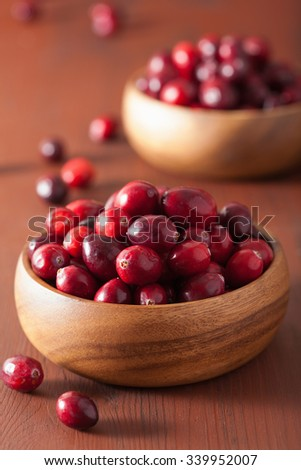 fresh cranberry in wooden bowls over rustic table - stock photo