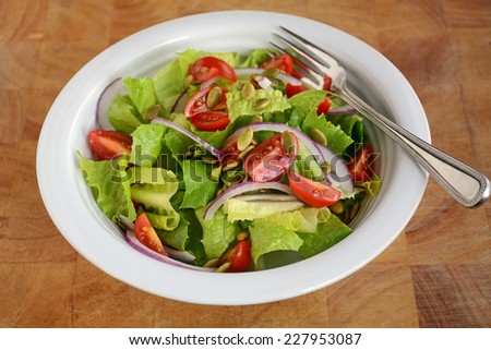 Fresh crisp romaine lettuce and cherry tomato salad with red onion and pumpkin seeds - stock photo