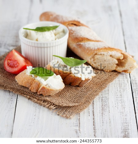 Fresh crispy baguette and cream cheese with herbs on white wooden background, selective focus - stock photo