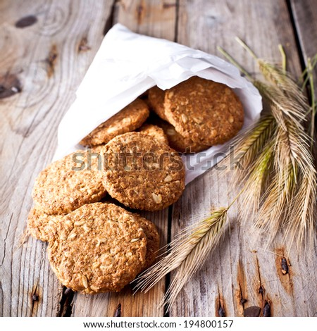 fresh crispy cereal cookies and ears on rustic wooden table  - stock photo