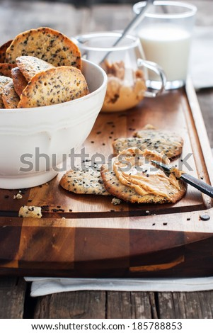 Fresh Crispy Cookies with Black Sesame Seeds and Peanut Butter as breakfast on chopping board - stock photo