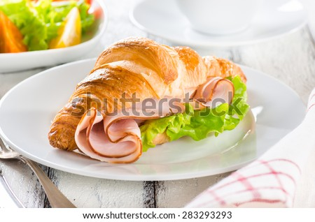 Fresh croissant with ham and salad leaf with fresh salad on white - stock photo