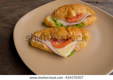 Fresh croissant with ham cheese and salad leaf with fresh salad in dish on wooden texture - France food - stock photo