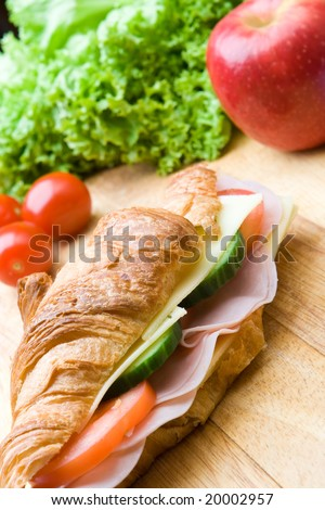 Fresh croissant with ham, cheese, salad and a red apple - stock photo
