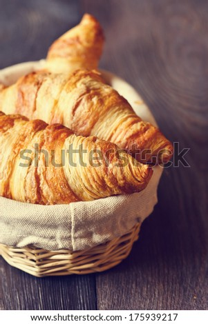Fresh croissants for breakfast in a basket on a wooden background. Toned photo. - stock photo