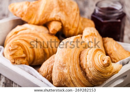 Fresh Croissants on wooden rustic background - stock photo