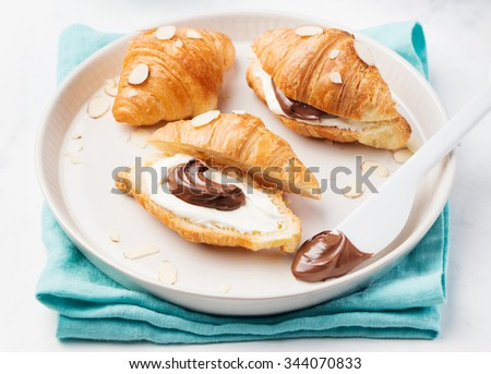 Fresh croissants with cream cheese and chocolate and nut cream on plate on a white background - stock photo