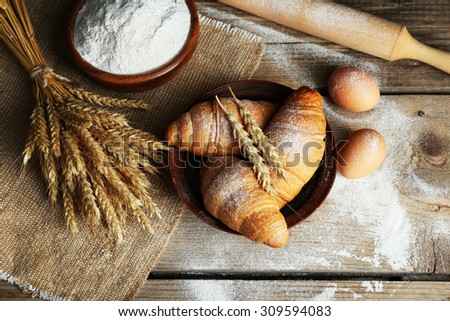 Fresh croissants with flour on wooden table, top view - stock photo